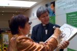 Pater Patzig mit sprechendem Bild und Zuschauerin